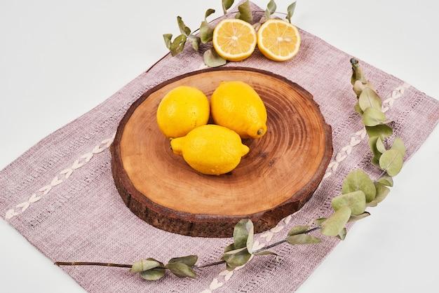 Limões em uma bandeja de madeira com folhas.