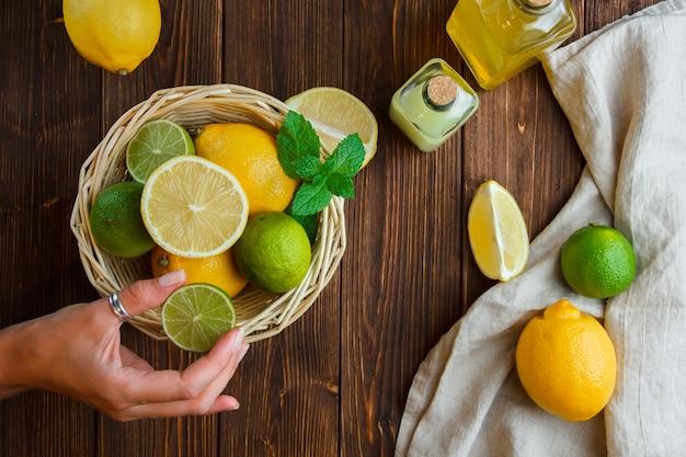 Limões em uma cesta com a mão de um pano branco segurando metade da vista superior do limão em uma superfície de madeira