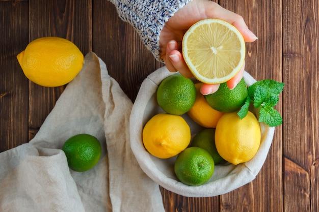 Limões em uma cesta com pano branco, mãos segurando a vista superior do limão em uma superfície de madeira