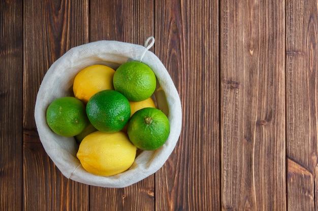 Limões em uma cesta com um pano branco sobre um fundo de madeira. vista do topo. espaço para texto