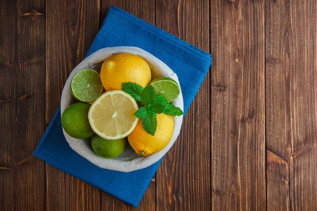 Limões em uma cesta com vista superior de um pano azul em uma superfície de madeira