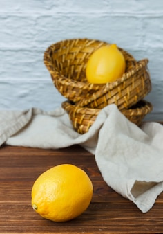Limões em uma cestas sobre uma superfície de madeira. vista de alto ângulo. espaço para texto
