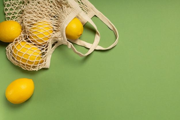 Limões em uma sacola ecológica em uma superfície verde