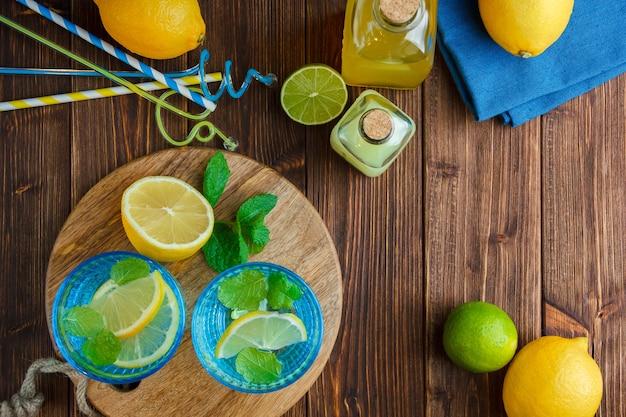 Limões em uma tigela com pano azul, faca de madeira e garrafa de suco, canudos, vista superior de uma superfície de madeira