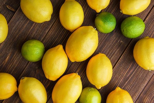 Limões espalhados com limas em uma mesa de madeira. configuração plana.