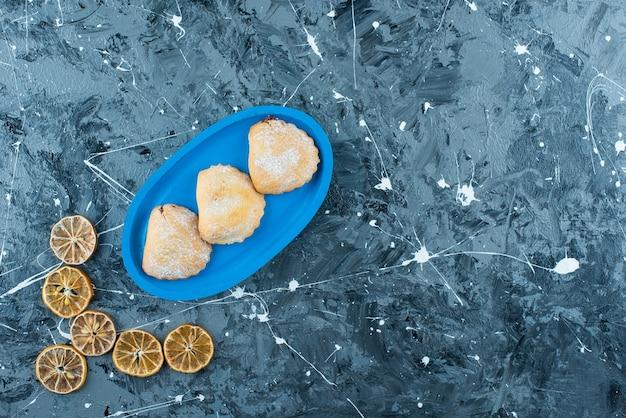 Limões fatiados ao lado de bolos na placa de madeira, na mesa azul.