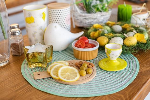 Limões fatiados, azeitonas, amêndoas em uma placa de madeira, ovos de páscoa na grande mesa familiar