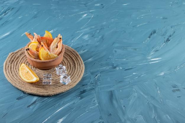 Limões fatiados e camarões em uma tigela sobre um tripé, no fundo de mármore.