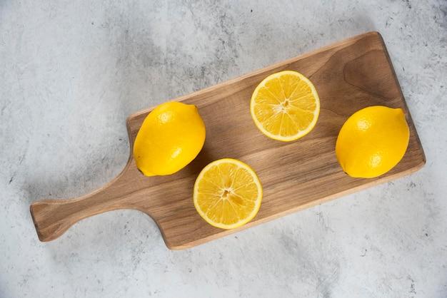 Limões fatiados e inteiros com escareador de madeira.