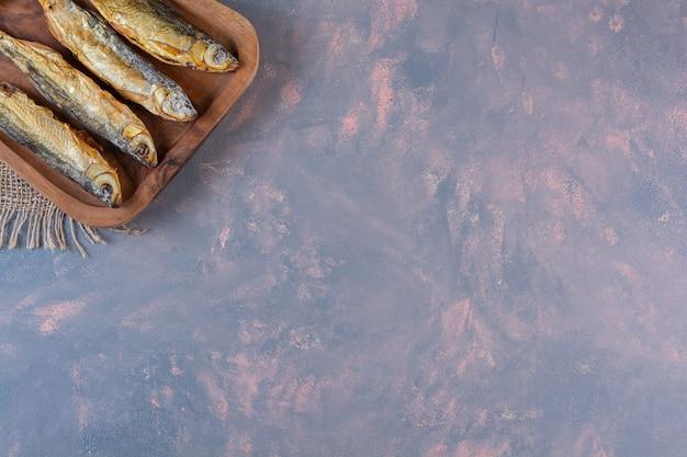 Limões fatiados e peixe salgado em uma tábua de cortar em um guardanapo de estopa, na superfície de mármore