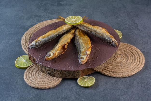 Limões fatiados e peixes salgados secos em uma placa sobre um tripé, na superfície de mármore