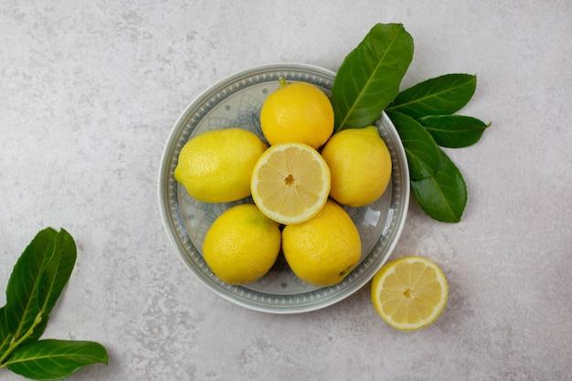 Limões frescos com folhas em um prato na superfície de concreto cinza claro