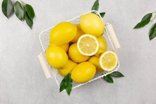 Limões frescos com folhas em uma cesta branca em uma superfície de concreto cinza claro
