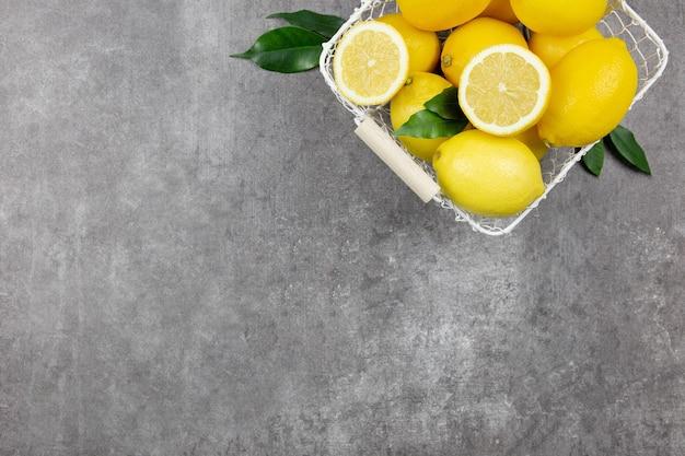 Limões frescos com folhas em uma cesta branca na superfície de concreto cinza escuro