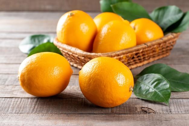 Limões frescos com folhas em uma mesa de madeira