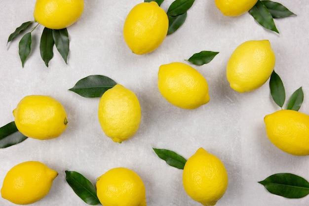 Limões frescos com folhas na superfície de concreto cinza claro