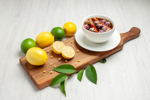 Limões frescos de vista frontal com uma xícara de chá na mesa branca cítricos limão suco fresco azedo