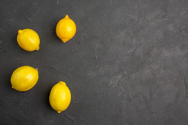 Limões frescos de vista superior alinhados na mesa escura com espaço livre de frutas cítricas amarelas para texto