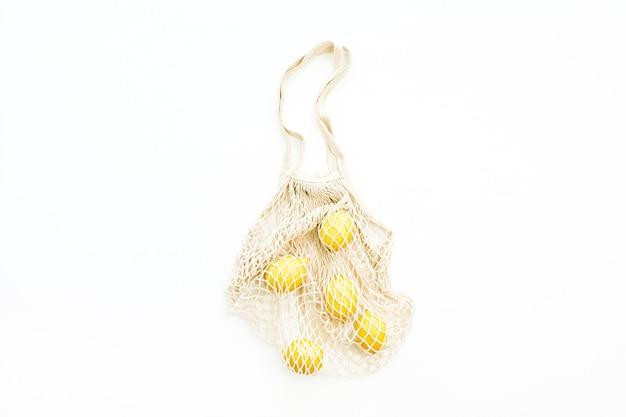 Limões frescos e crus em um saco de barbante em fundo branco. camada plana, vista superior
