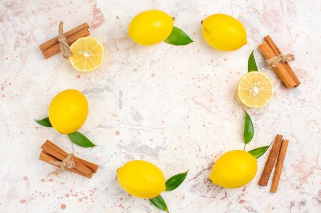 Limões frescos em forma de círculo cortados em palitos de canela em uma superfície isolada brilhante no espaço livre