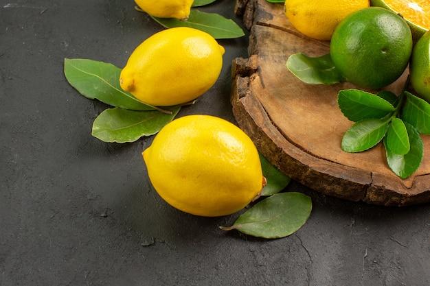 Limões frescos em piso escuro com limão azedo de frutas cítricas
