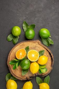 Limões frescos em piso escuro com limão e frutas cítricas