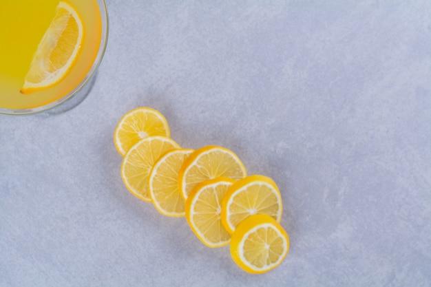 Limões frescos fatiados ao lado de um copo de suco de laranja na mesa de mármore.