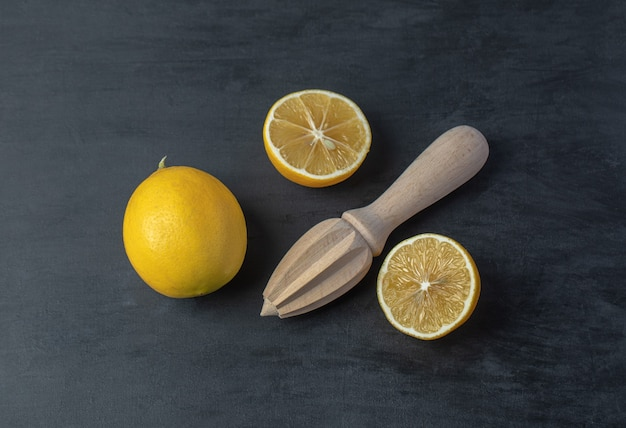 Limões frescos fatiados e inteiros amarelos com um alargador de madeira.