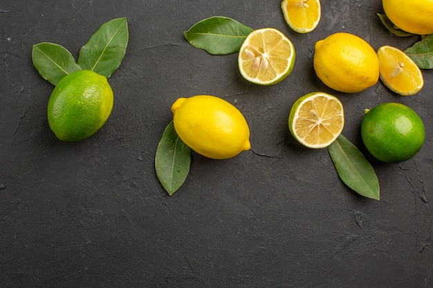 Limões frescos, frutas ácidas em piso escuro e lima cítrica