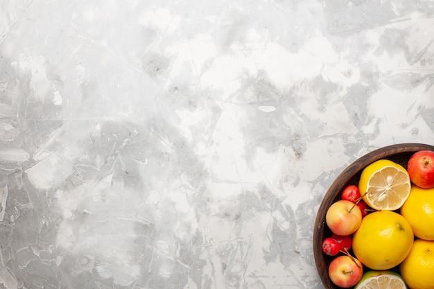 Limões frescos inteiros e fatiados em um espaço em branco claro