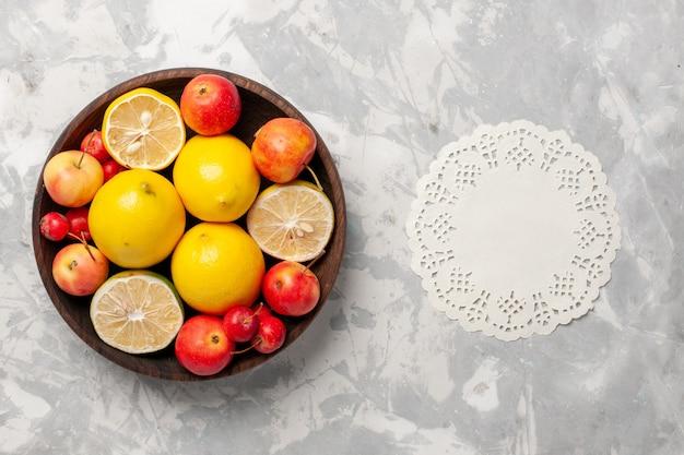 Limões frescos inteiros e fatiados na mesa branca de cima