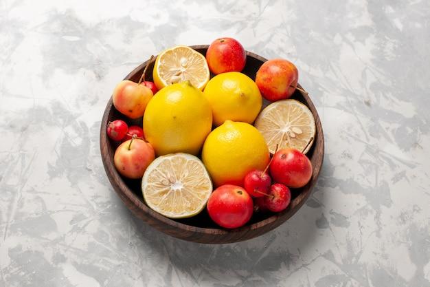 Limões frescos inteiros e fatiados no espaço em branco de vista frontal