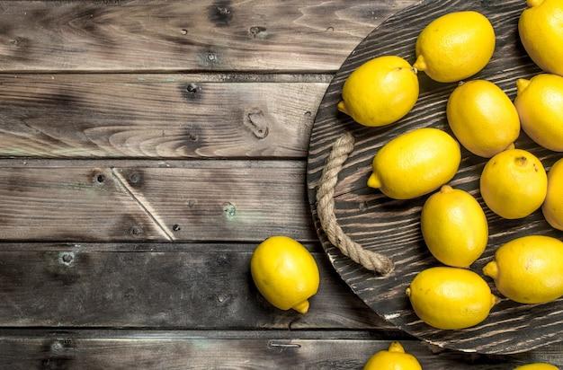 Limões frescos na bandeja. em fundo de madeira