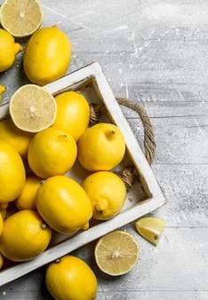 Limões frescos na bandeja. em uma superfície rústica branca