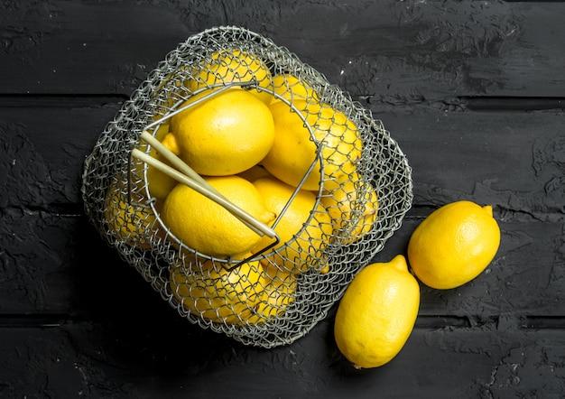 Limões frescos na cesta de ferro na mesa rústica.