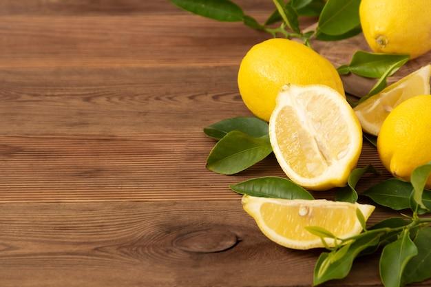 Limões frescos na mesa de madeira rústica. frutas cítricas com folhas.