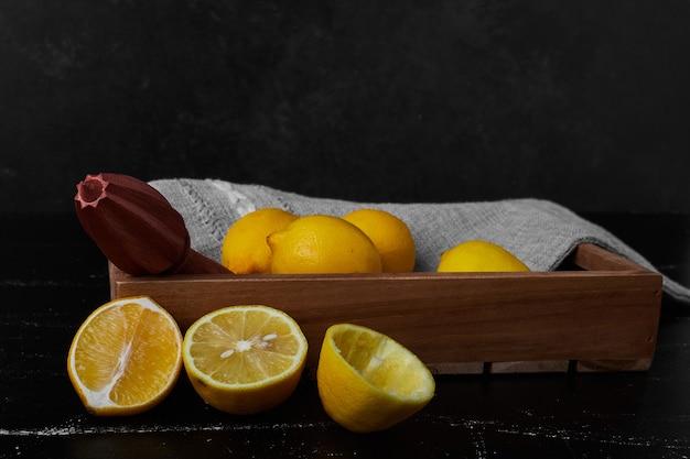 Limões isolados em uma bandeja de madeira.