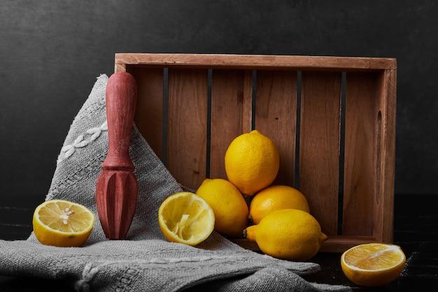Limões isolados em uma parede preta em uma bandeja de madeira.