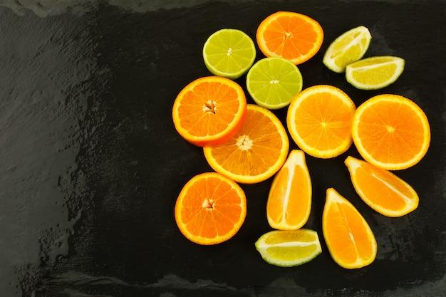Limões, laranjas e limões em fundo preto, copie o espaço