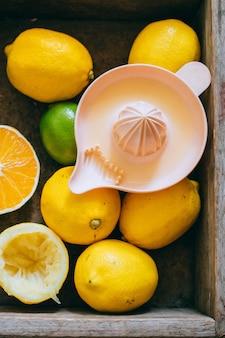 Limões, limão, laranja em uma caixa de madeira, um espremedor de citrinos. limonada fresca.