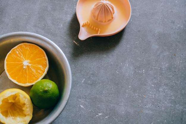 Limões, limão, laranja em uma placa de cerâmica branca com um padrão, um espremedor de citrinos