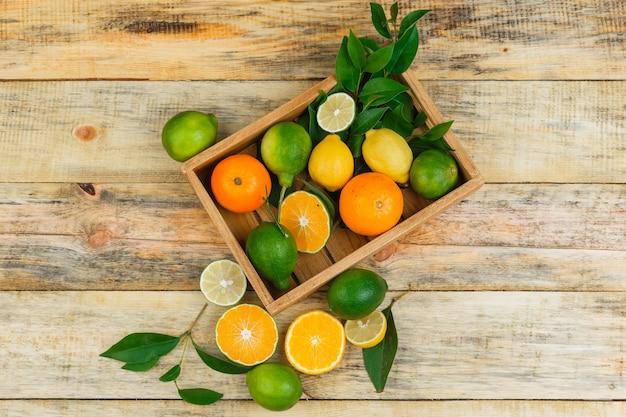 Limões, limas e laranjas em uma caixa de madeira com folhas