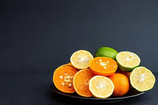 Limões, limas e tangerinas inteiras e metades em placas pretas em uma mesa preta