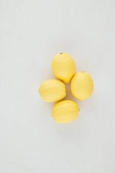 Limões maduros e suculentos em fundo cinza claro para uma bebida vitamínica ou limonada