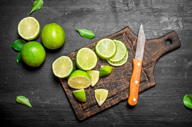Limões maduros em uma placa de corte com uma faca.