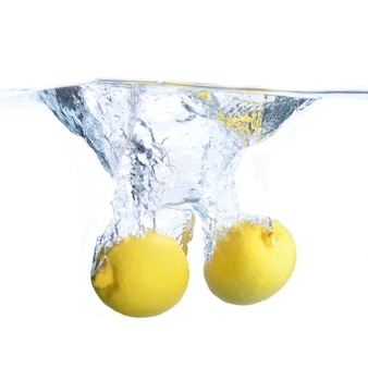 Limões na água com bolhas e salpicos. fechar-se. isolado no branco. conceito e idéia com limões
