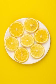 Limões, pedaços maduros de suculentos maduros frescos cortados dentro da placa-de-rosa na mesa amarela