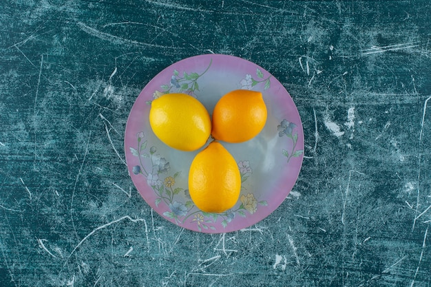 Limões saborosos no prato, na mesa de mármore.
