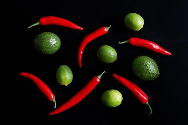Limões suculentos, abacate e pimenta em um fundo preto