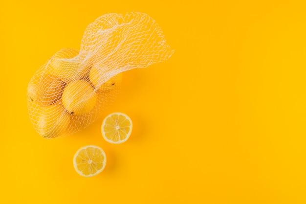 Limões suculentos cortados ao meio e inteiros no fundo amarelo